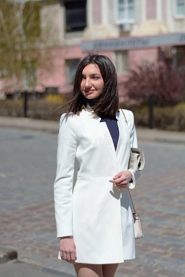 Mujer joven elegante en una calle de la ciudad con un peri?dico en sus manos imagen de archivo