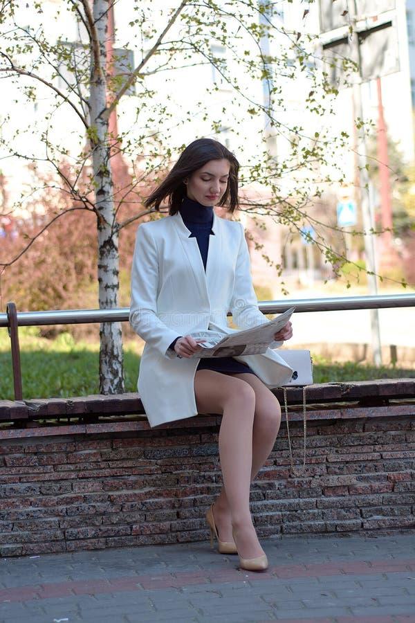 Mujer joven elegante en una calle de la ciudad con un peri?dico en sus manos imagen de archivo libre de regalías