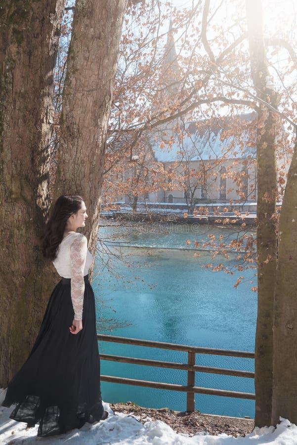 Mujer joven elegante encendido a orillas del lago foto de archivo