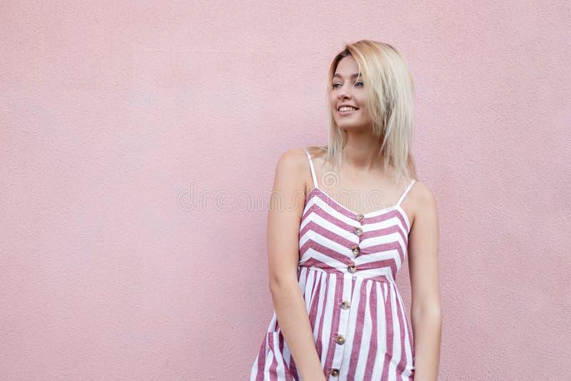 Mujer joven elegante feliz moderna rubia con sonrisa linda en el vestido rayado de moda que presenta cerca de una pared rosada de foto de archivo libre de regalías