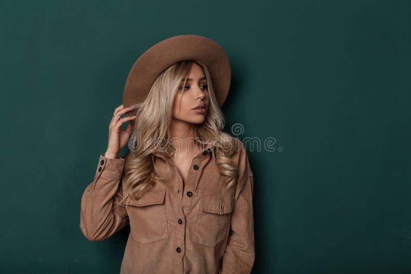 Mujer joven elegante hermosa con el pelo rizado en un sombrero beige elegante del vintage en una camisa de moda con la presentaci fotos de archivo