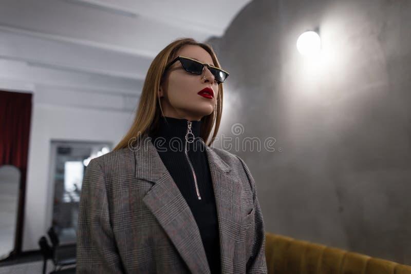 Mujer joven elegante hermosa del inconformista que sorprende en gafas de sol de moda negras en chaqueta a cuadros elegante gris c fotos de archivo libres de regalías