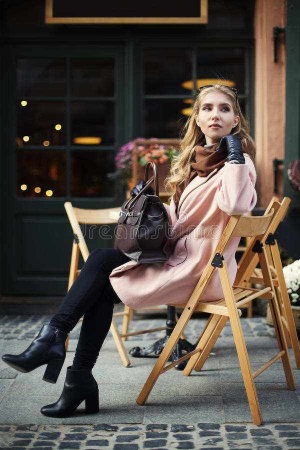 Mujer joven elegante hermosa que se sienta en café de la calle Forma de vida de la ciudad Moda femenina Retrato lleno de la carro imagen de archivo