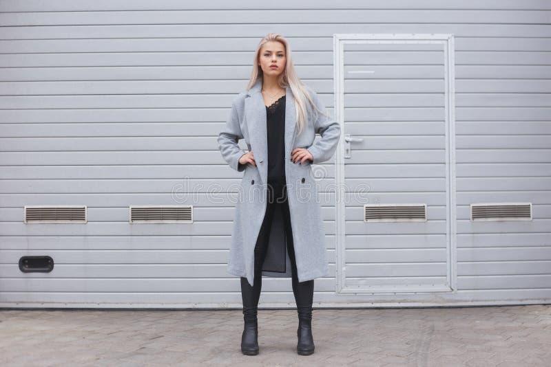 Mujer joven elegante que lleva la capa gris que presenta contra la pared áspera de la calle, estilo urbano minimalista de la ropa imagen de archivo libre de regalías