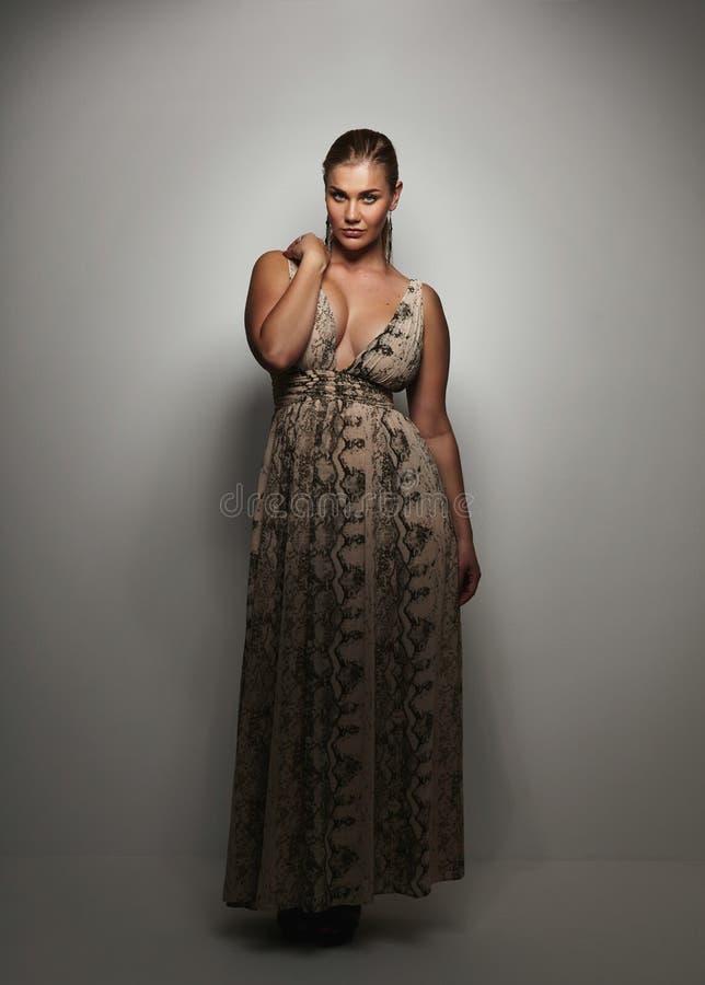 Mujer joven elegante que presenta en un vestido de noche fotos de archivo libres de regalías