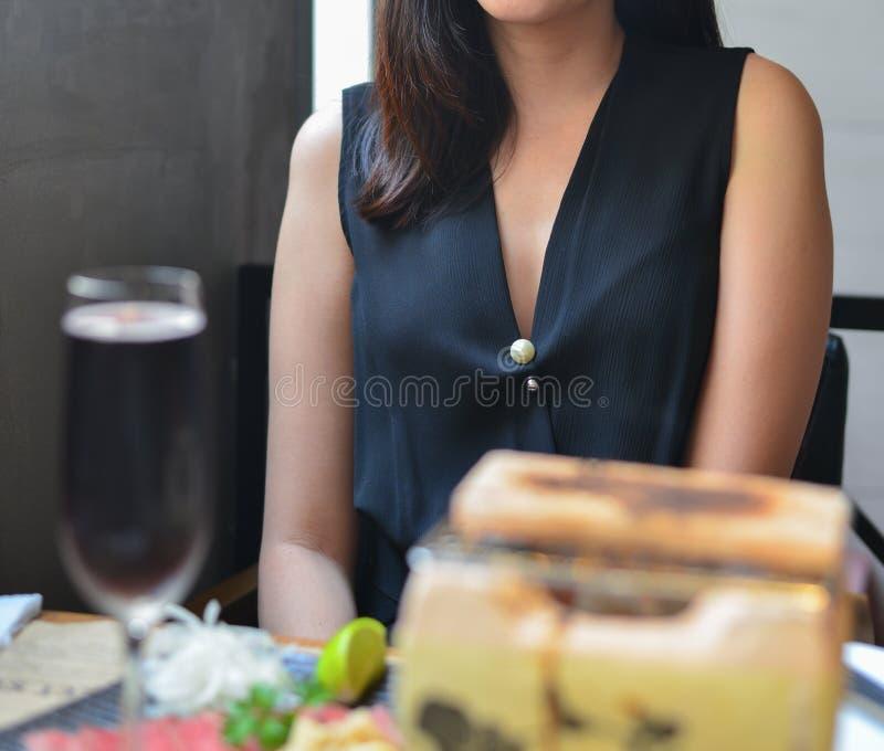 Mujer joven elegante que se sienta en restaurante foto de archivo libre de regalías