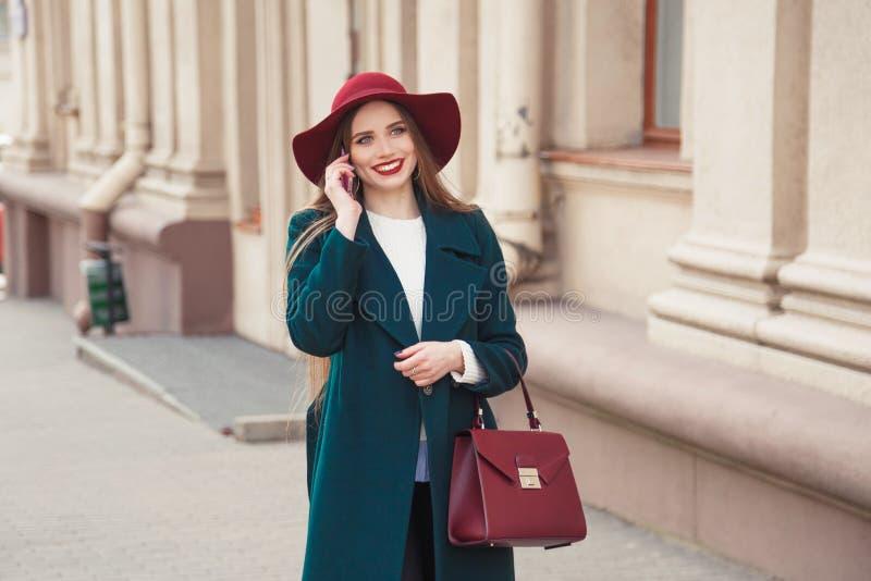 Mujer joven elegante vestida hermosa que sonríe mientras que habla en el teléfono al aire libre foto de archivo libre de regalías