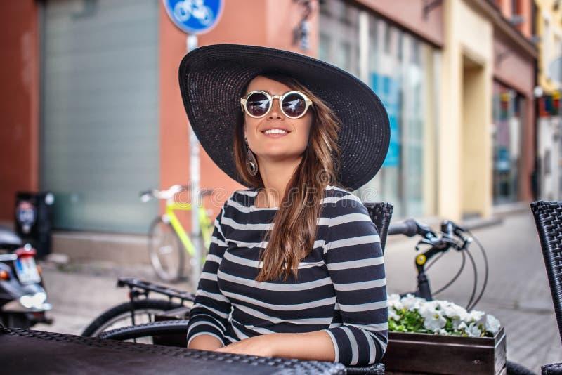 Mujer joven elegante vestida que lleva un sombrero elegante y las gafas de sol que se sientan en un café de la calle del verano fotos de archivo libres de regalías