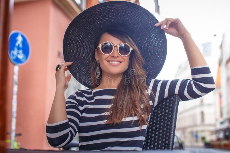 Mujer joven elegante vestida que lleva un sombrero elegante y las gafas de sol que se sientan en un café de la calle del verano fotografía de archivo