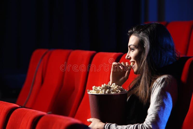 Mujer joven, ella come las palomitas y sonríe imagen de archivo libre de regalías