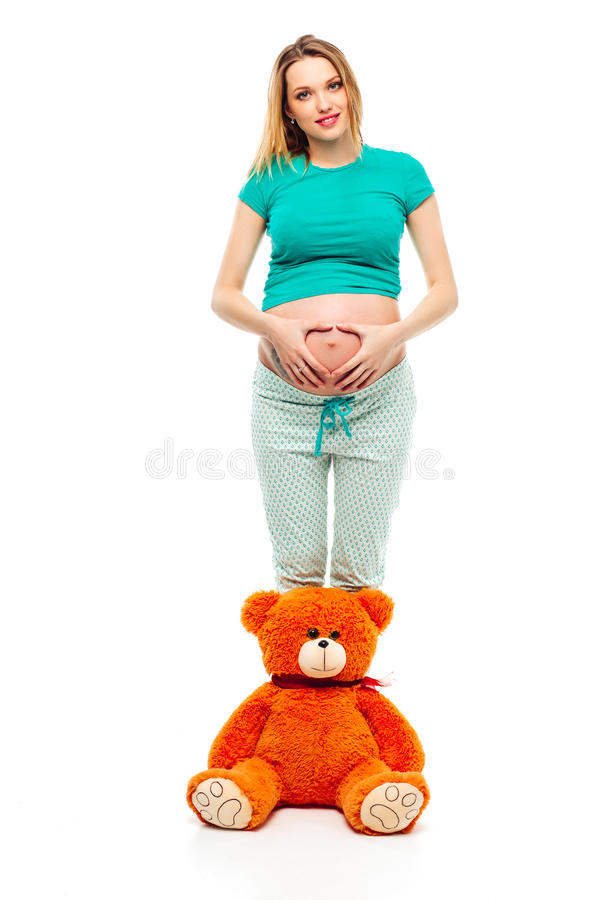 Mujer joven embarazada en el fondo blanco que hace un corazón en su estómago, un oso suave del juguete cerca de sus piernas Sonri imágenes de archivo libres de regalías