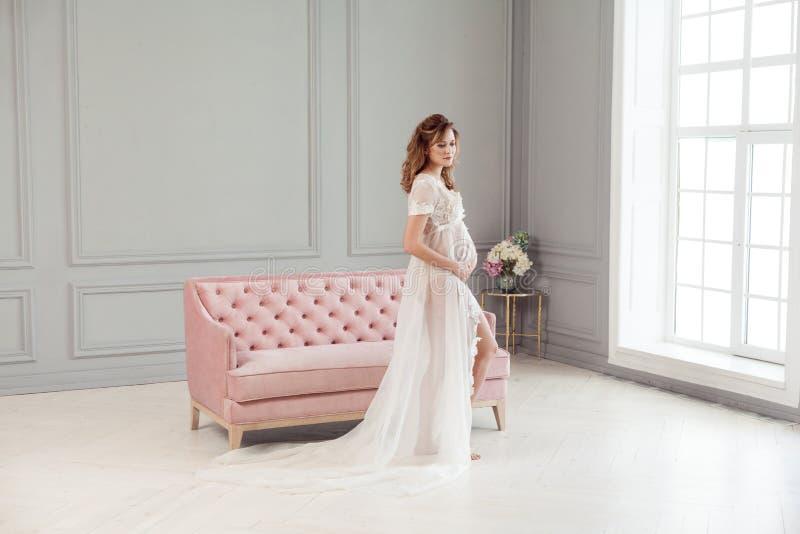 Mujer joven embarazada hermosa en el peignoir blanco del vestido que se coloca cerca del sofá rosado, sosteniéndose con amor el v foto de archivo