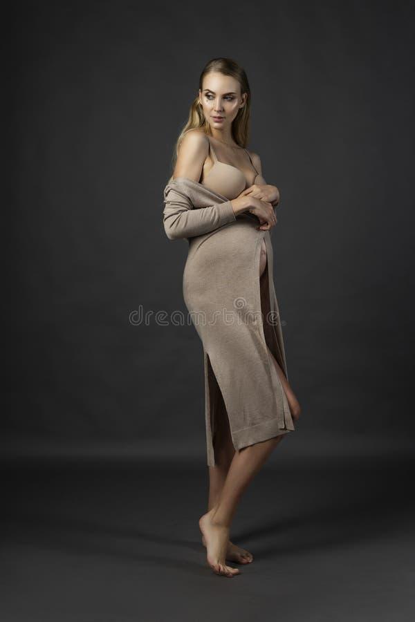 Mujer joven embarazada hermosa, llevando una ropa interior y un b hecho punto foto de archivo libre de regalías