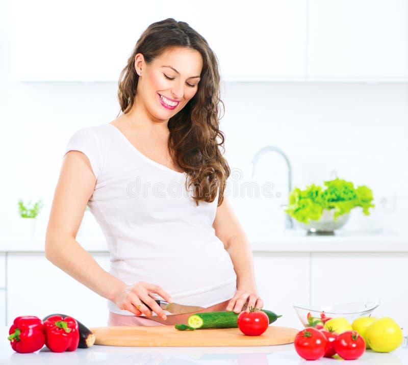 Mujer joven embarazada que cocina verduras fotografía de archivo