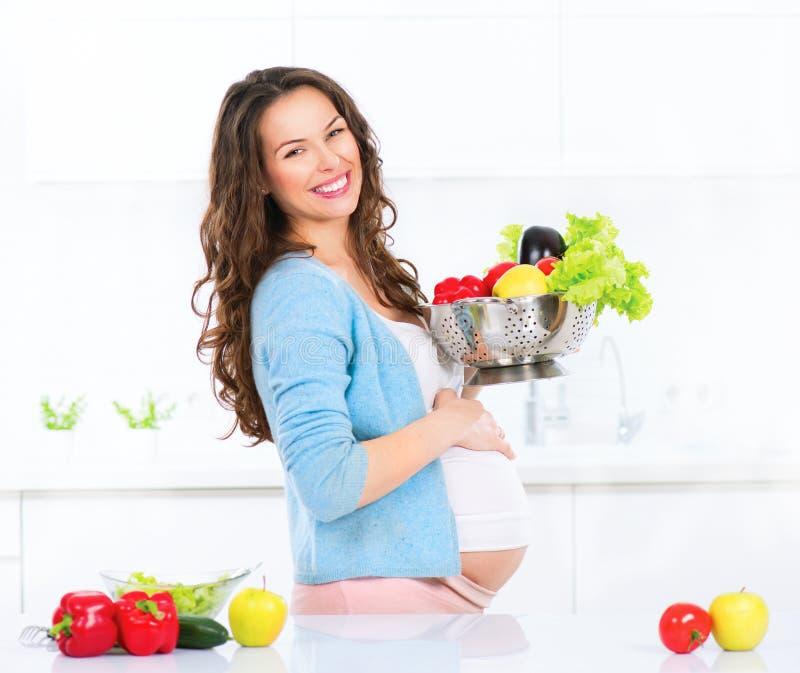Mujer joven embarazada que cocina verduras imagen de archivo