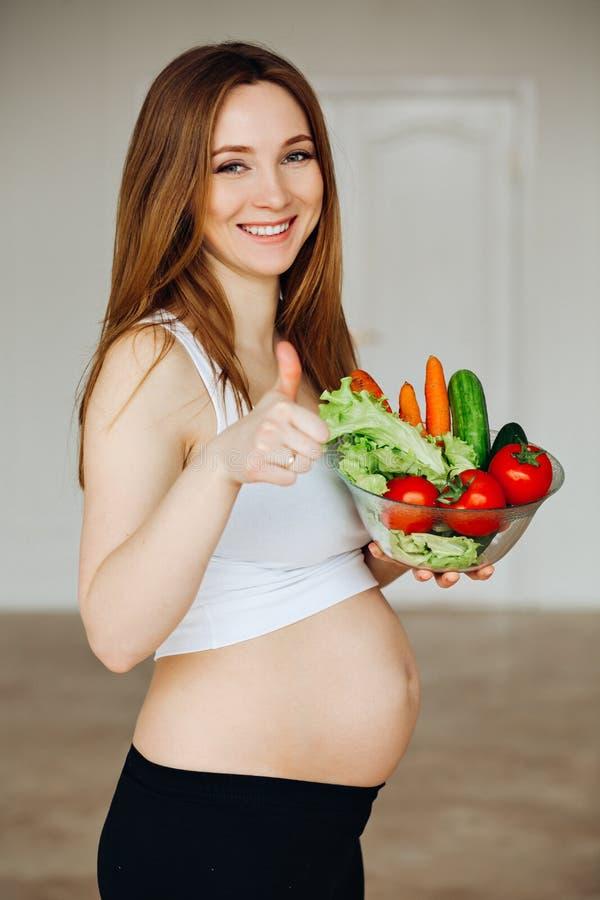 Mujer joven embarazada que cocina verduras Comida sana - ensalada vegetal Dieta Concepto de dieta Forma de vida sana foto de archivo libre de regalías