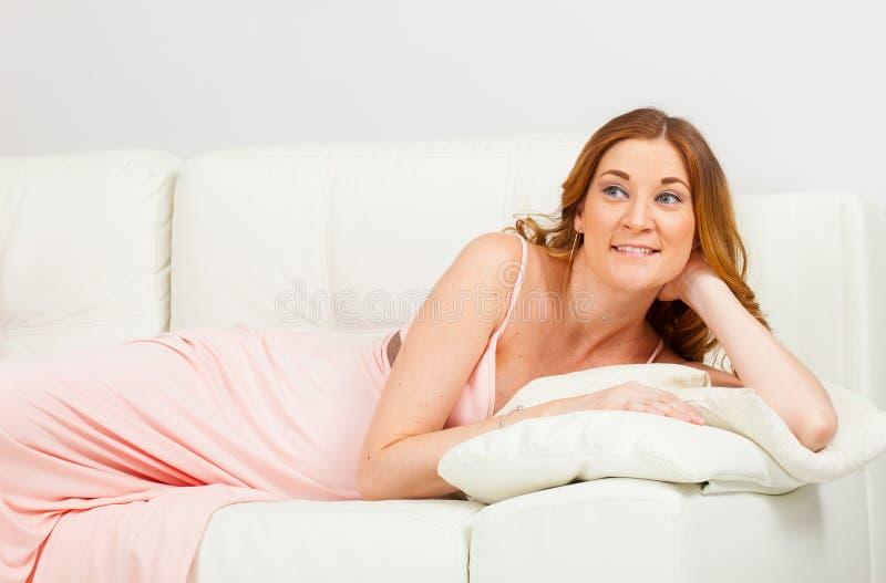 Mujer joven embarazada que miente en el sofá y la sonrisa blancos fotos de archivo libres de regalías
