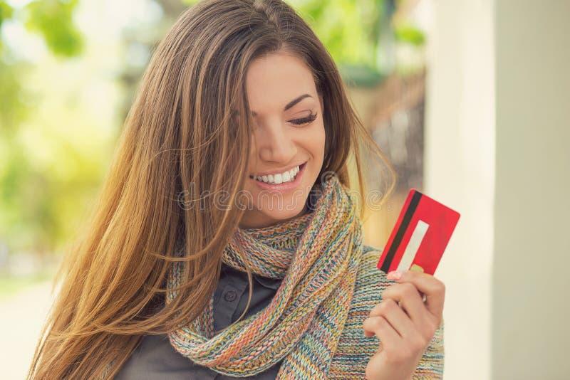 Mujer joven emocionada alegre con la tarjeta de crédito que se coloca al aire libre imagenes de archivo