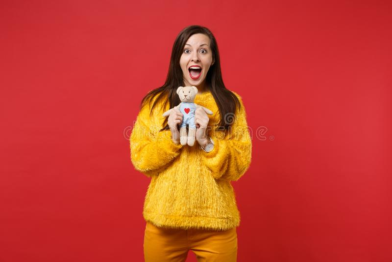 Mujer joven emocionada en el juguete abierto de par en par de la felpa del oso de peluche de la piel que se sostiene del suéter d fotografía de archivo