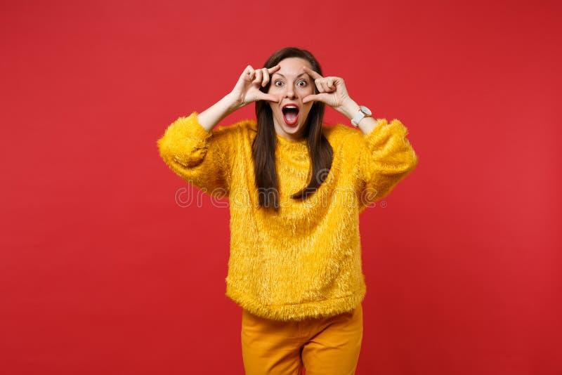 Mujer joven emocionada en el suéter amarillo de la piel que mantiene la boca abierta de par en par, estirando los párpados aislad foto de archivo libre de regalías