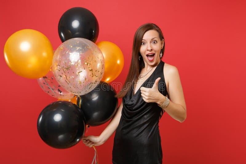 Mujer joven emocionada en poco vestido negro que celebra mostrando el pulgar encima de sostener los balones de aire aislados en r foto de archivo libre de regalías