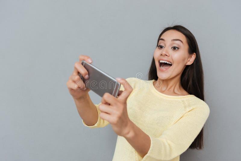 Mujer joven emocionada feliz que juega a los videojuegos en el teléfono celular fotos de archivo