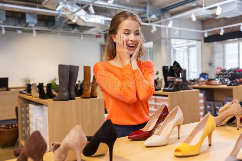 Mujer joven emocionada que elige los zapatos en la tienda fotos de archivo