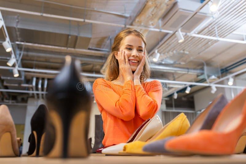 Mujer joven emocionada que elige los zapatos en la tienda fotografía de archivo