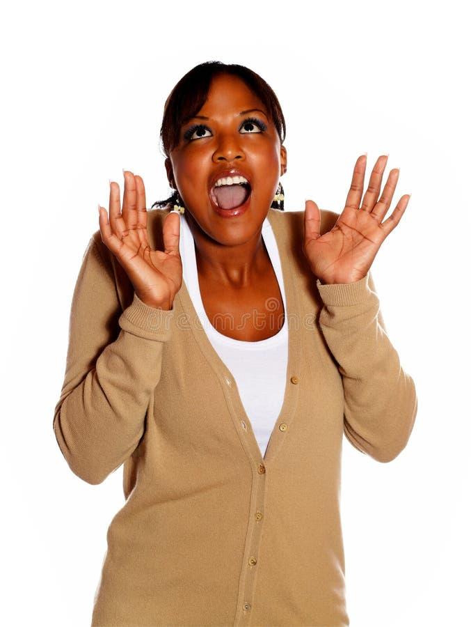 Mujer joven emocionada que grita con las manos para arriba foto de archivo libre de regalías