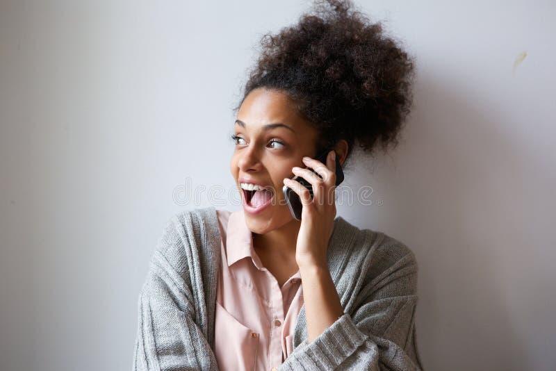 Mujer joven emocionada que habla en el teléfono móvil foto de archivo