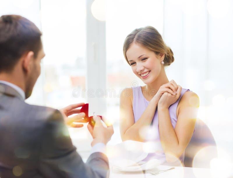 Mujer joven emocionada que mira al novio con el anillo imagen de archivo libre de regalías