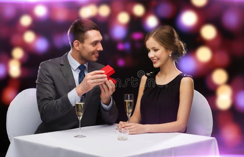 Mujer joven emocionada que mira al novio con la caja fotografía de archivo