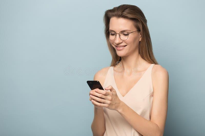Mujer joven emocionada usando el tel?fono m?vil conseguir el mensaje agradable fotografía de archivo