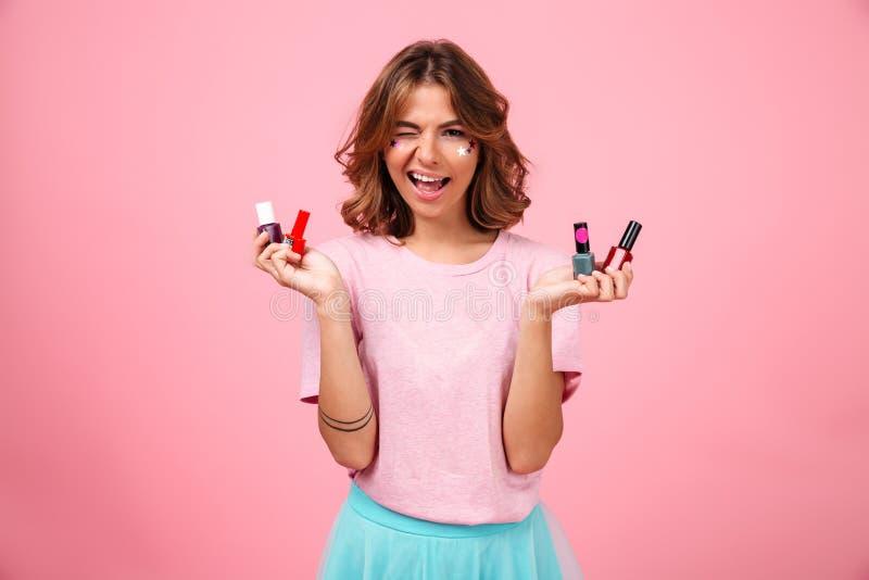 Mujer joven emocional alegre que lleva a cabo esmalte de uñas imagenes de archivo