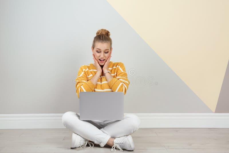 Mujer joven emocional con el ordenador portátil en piso cerca de la pared del color imagenes de archivo