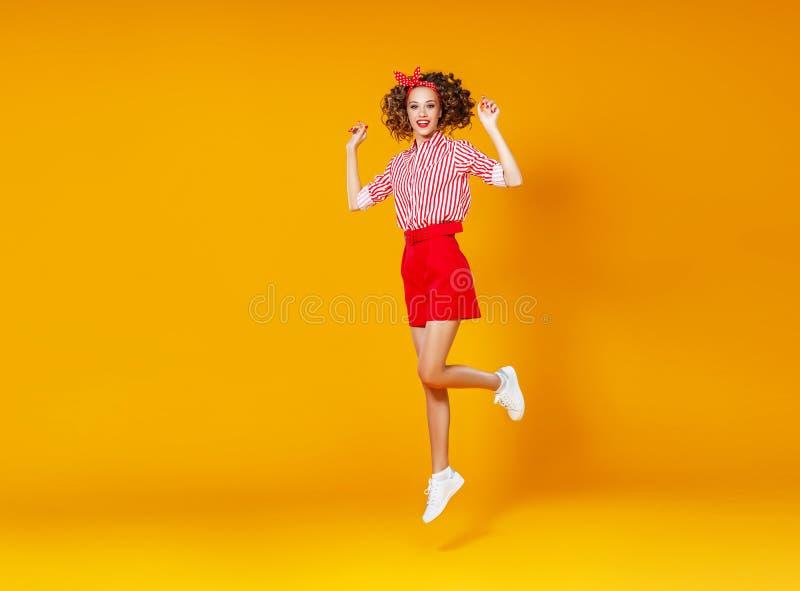 mujer joven emocional feliz del concepto en el salto rojo en fondo amarillo imagen de archivo libre de regalías