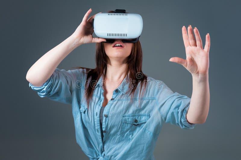 Mujer joven emocional que usa auriculares de VR y experimentando realidad virtual en fondo gris foto de archivo libre de regalías
