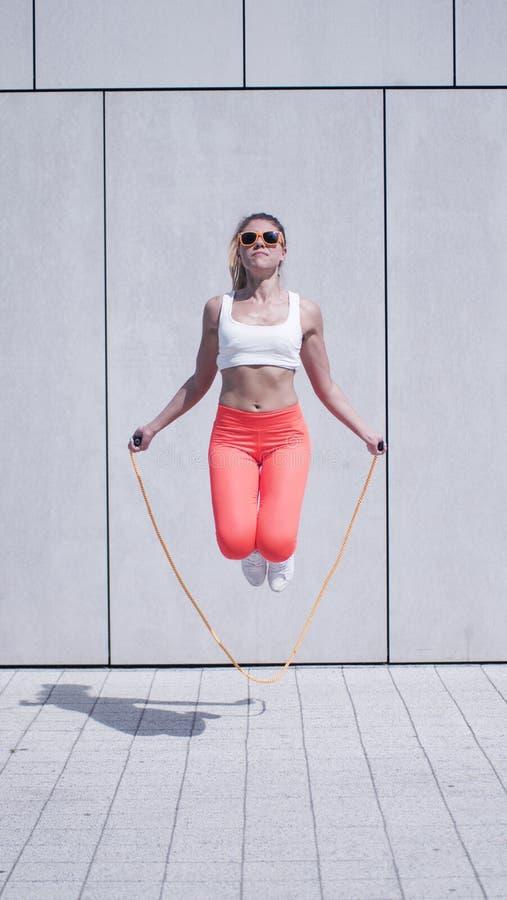 Mujer joven enérgica que ejercita con la cuerda de salto foto de archivo