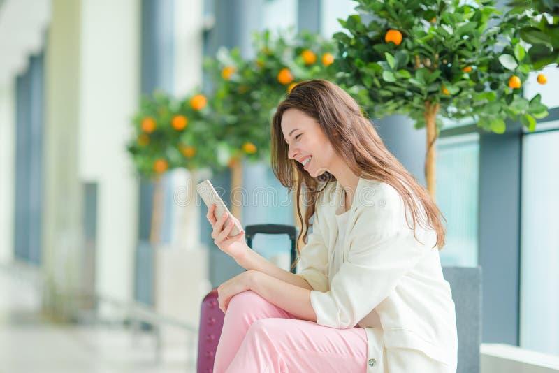 Mujer joven en aeropuerto internacional con su equipaje y smartphone que esperan su vuelo imágenes de archivo libres de regalías