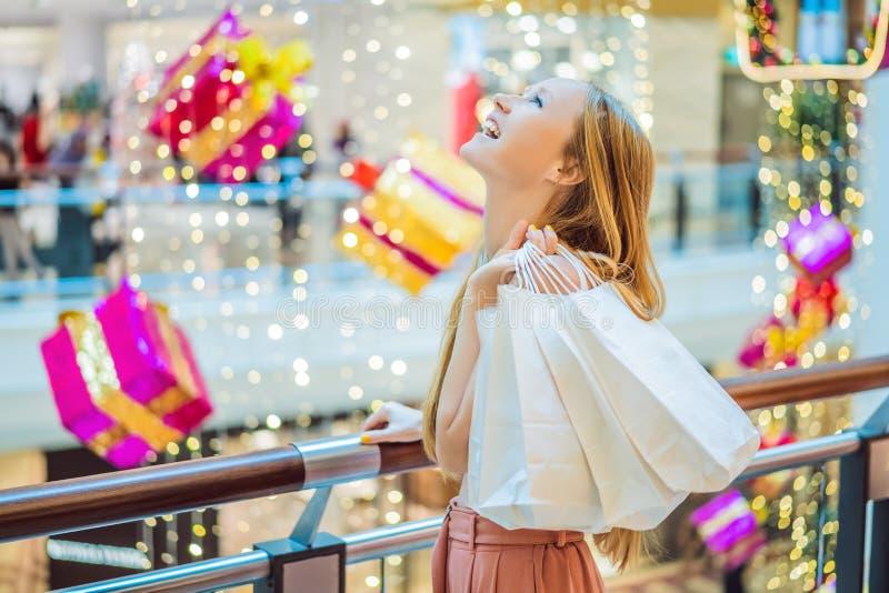 Mujer joven en alameda de la Navidad con compras de la Navidad Descuentos de las compras de la noche de la Navidad de la compra d fotografía de archivo libre de regalías