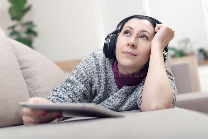 Mujer joven en auriculares con PC de la tableta en el sofá imagenes de archivo