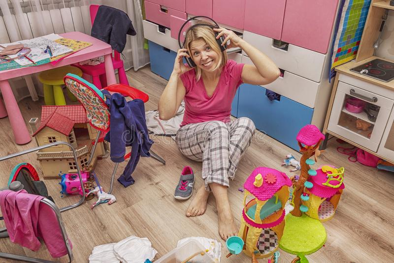 Mujer joven en auriculares en un cuarto de lío fotografía de archivo