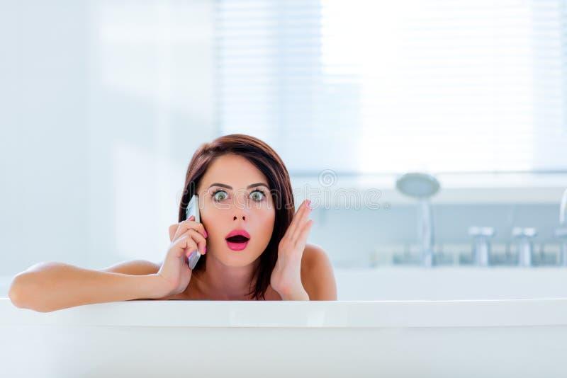 Mujer joven en baño con el teléfono imagenes de archivo