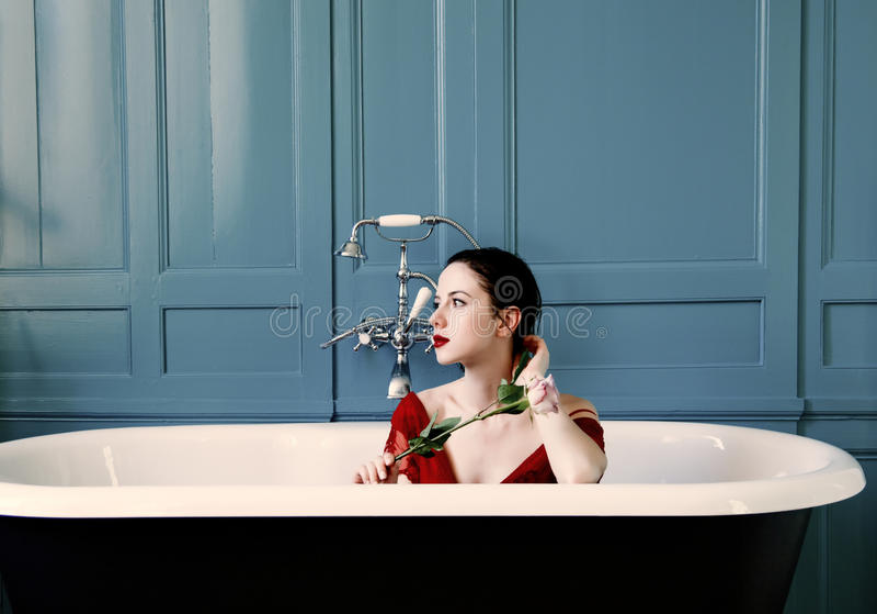 Mujer joven en baño con la flor fotografía de archivo libre de regalías