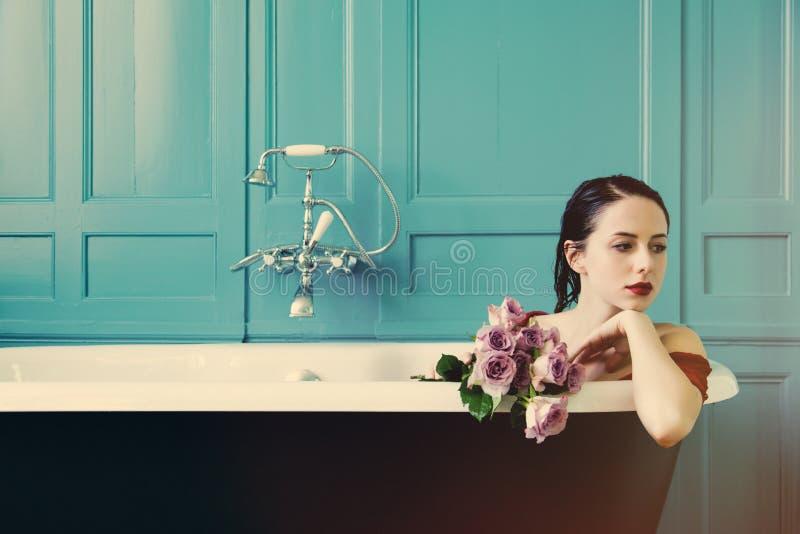 Mujer joven en baño con las flores imagenes de archivo