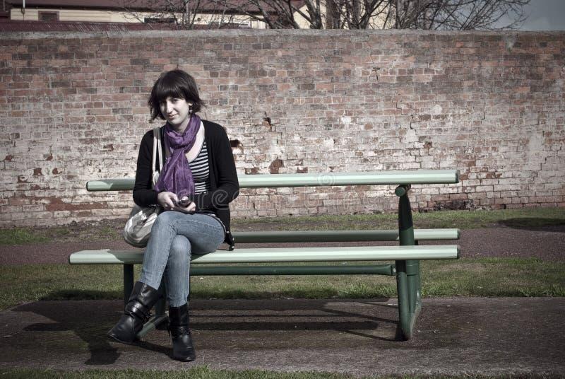 Mujer joven en banco de parque. imagen de archivo