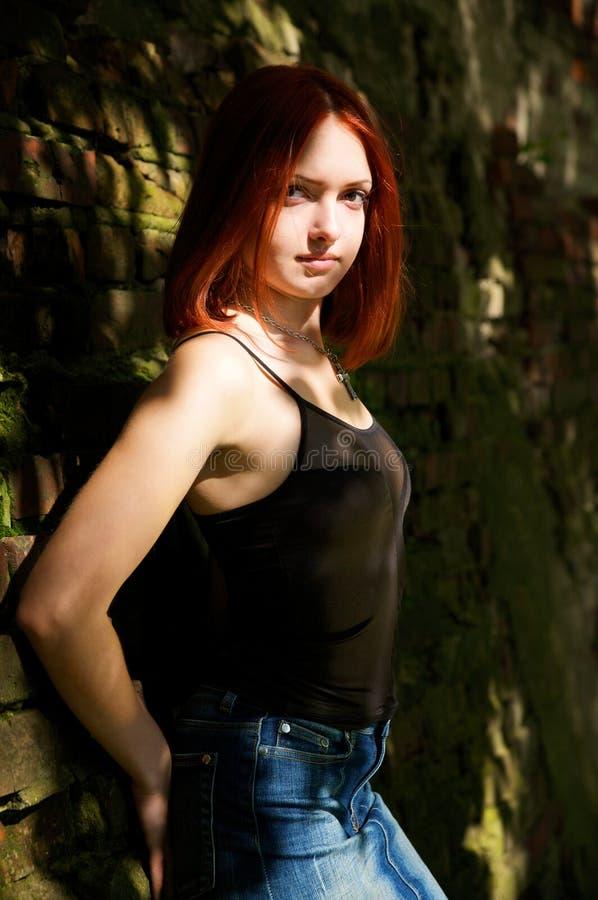 Mujer joven en brickwall sucio foto de archivo libre de regalías