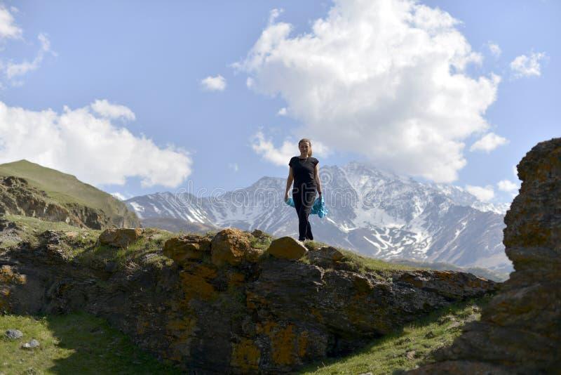 Mujer joven en camiseta entre las montañas nevosas fotografía de archivo libre de regalías