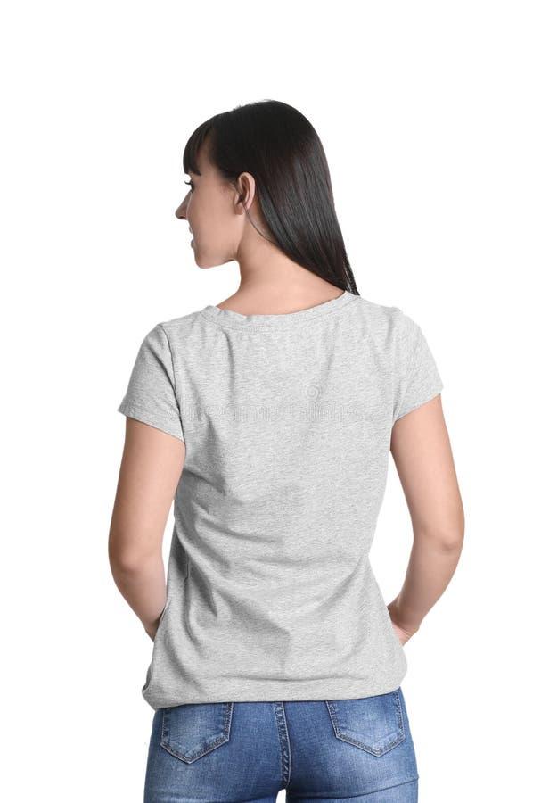 Mujer joven en camiseta gris en el fondo blanco foto de archivo