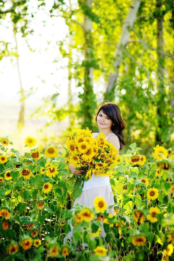 Mujer joven en campo floreciente del girasol fotografía de archivo